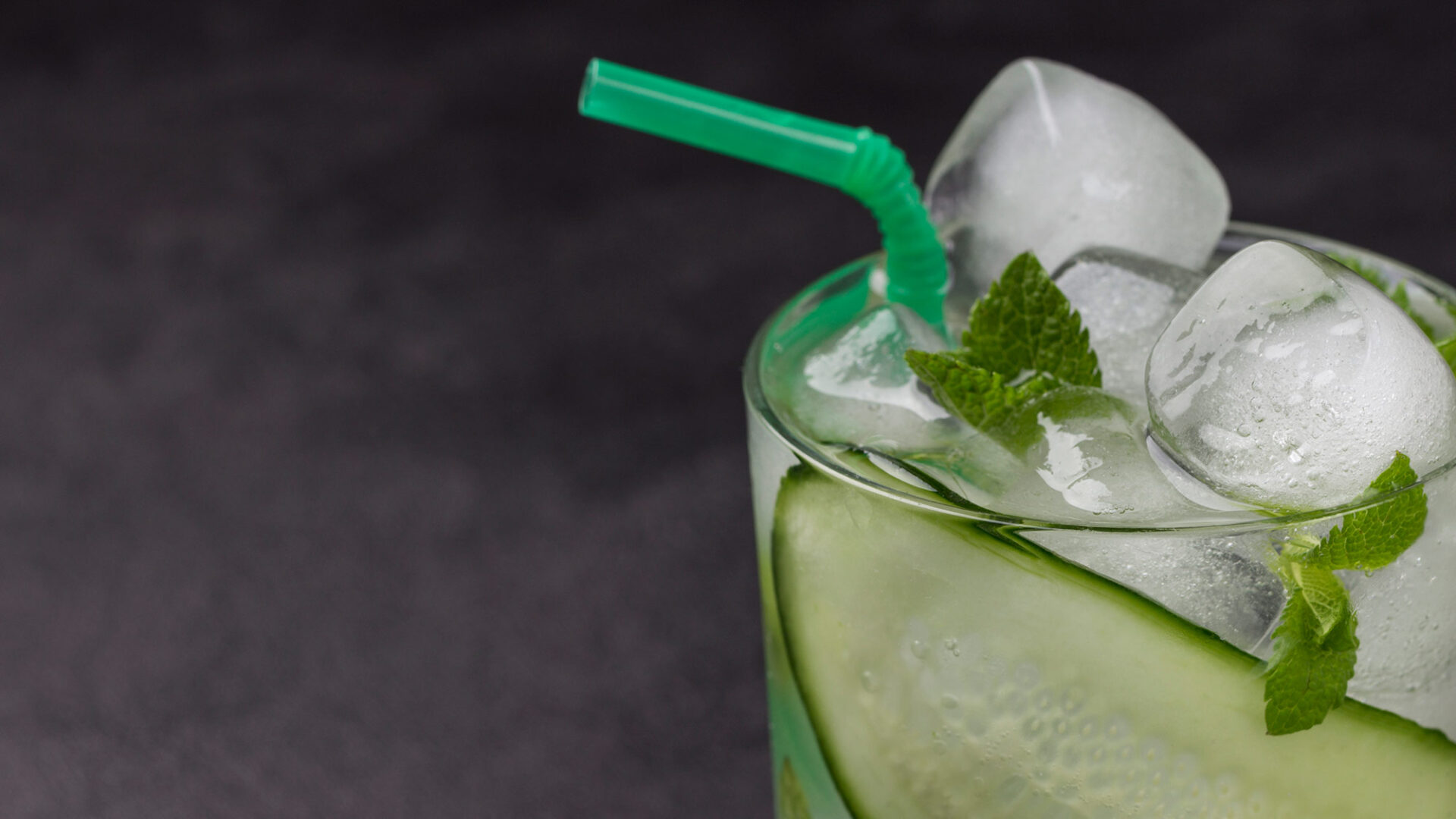 cooling summer drink with ice slices cucumber mint chopped cucumber black background copy space 16 9
